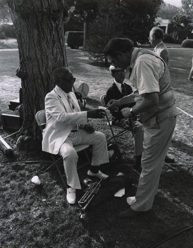 Zoot Sims slips a little hooch into Roy Eldridge's cup as Doc Cheatham looks on