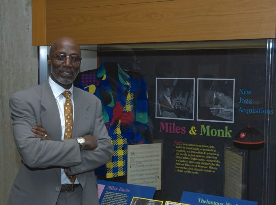 """Thelonius Monk Jr. poses in front of the new display, """"Miles and Monk: New Jazz Acquisitions,"""" at the Smithsonian's National Museum of American History image 0"""