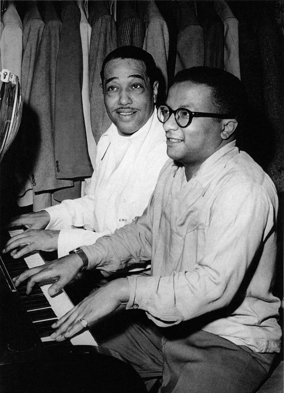 """Duke Ellington and Strayhorn playing 4-handed piano, perhaps their favorite duet """"Tonk."""" Note Duke's suits in the background."""