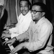 "Duke Ellington and Strayhorn playing 4-handed piano, perhaps their favorite duet ""Tonk."" Note Duke's suits in the background. image 0"