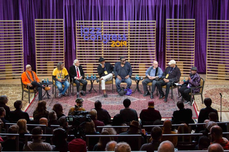 The Electric Miles panel at the 2019 Jazz Congress (L to R): Mtume, Mark Ruffin, Gary Bartz, Vince Wilburn, Jr., Wallace Roney, Dave Liebman, Michael Henderson, Lenny White